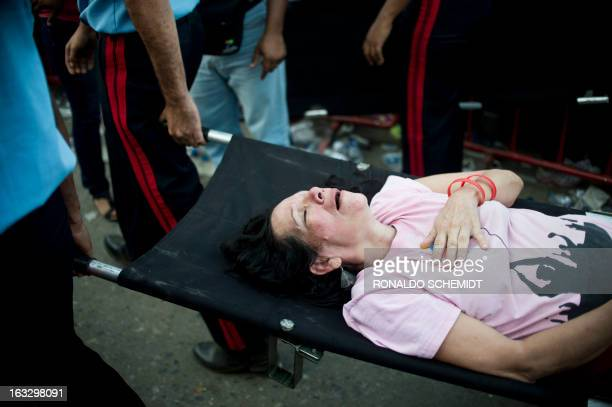 Guards carry a supporter as she fainted while waiting to pay respects to late Venezuelan President Hugo Chavez outside the Military Academy in...