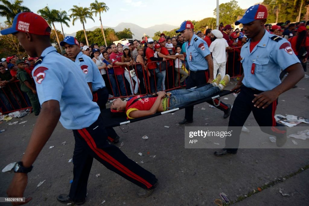 Guards carry a supporter who fainted as she waited in line to pay respects to late Venezuelan President Hugo Chavez, outside the Military Academy in Caracas on March 7, 2013. Venezuelans filed past the open casket of late President Hugo Chavez as he lay in state after throngs of weeping loyalists gave the firebrand leftist a rousing farewell on the streets on the eve. AFP PHOTO/Leo Ramirez