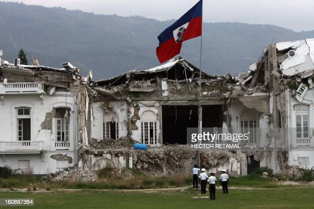 Guards raise the Haitian national flag outside the quakedestroyed ruins of the Presidential Palace on November 16 2010 in PortauPrince Haiti's...