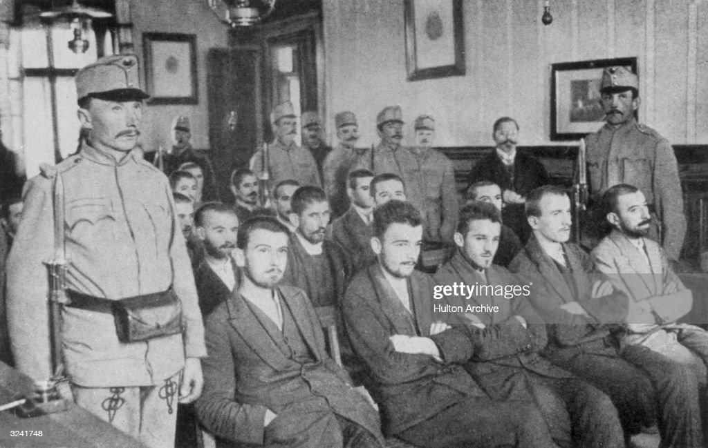 Guards stand alongside seated members of the Bosnian liberation group 'Young Bosnia,' during the trial of their member Gavrilo Princip, who was arrested for the assassination of the Austrian Archduke Franz Ferdinand and his wife, Sophie.
