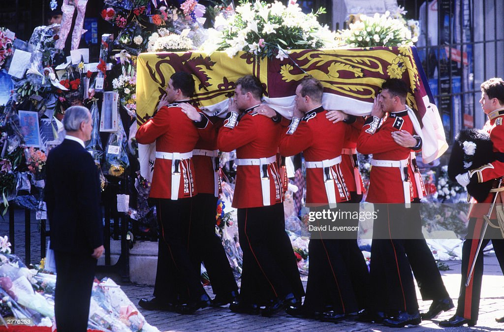 Guardsmen of the Prince of Wales Company of the Welsh Guards carry Princess Diana's coffin into Westminster Abbey on September 6, 1997 in London, England, during the funeral of Diana Princess of Wales. The coffin was draped with the Royal Standard,on top of it are three wreaths, from Prince William, Prince Harry and Earl Spencer.