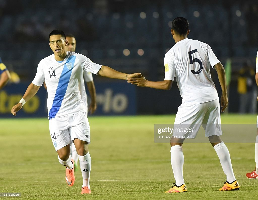 Guatamala's Rafael Morales is greeted by his teammate Moises Hernandez after score against USA in Guatemala City on March 25 2016 ahead of North and...