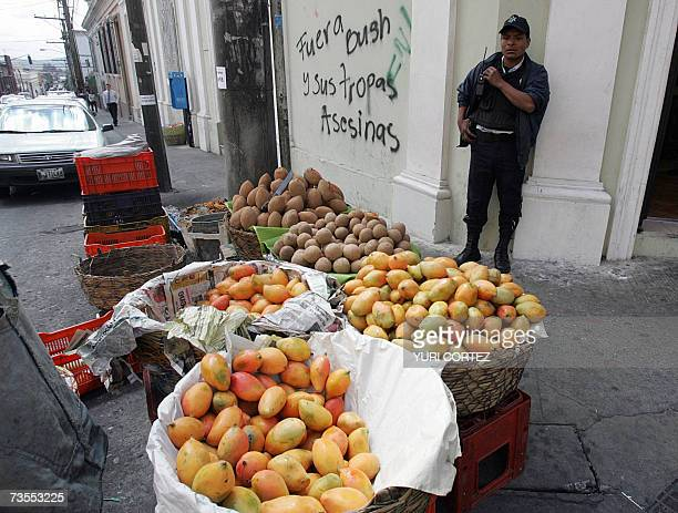 A Guatemalan security guard stands alert as a street vendor sells some fruits in front of a graffiti against the visit of the US president George W...