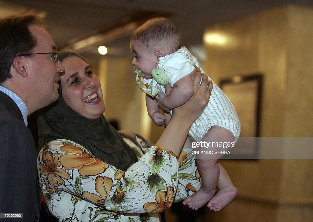 Egyptian Rania Elwani, member of the International Olympic Committee (IOC), presents her baby to US Roberto Fasulo at the end of the 119th IOC Session on July 7th, 2007 in Guatemala City. AFP PHOTO/Orlando SIERRA
