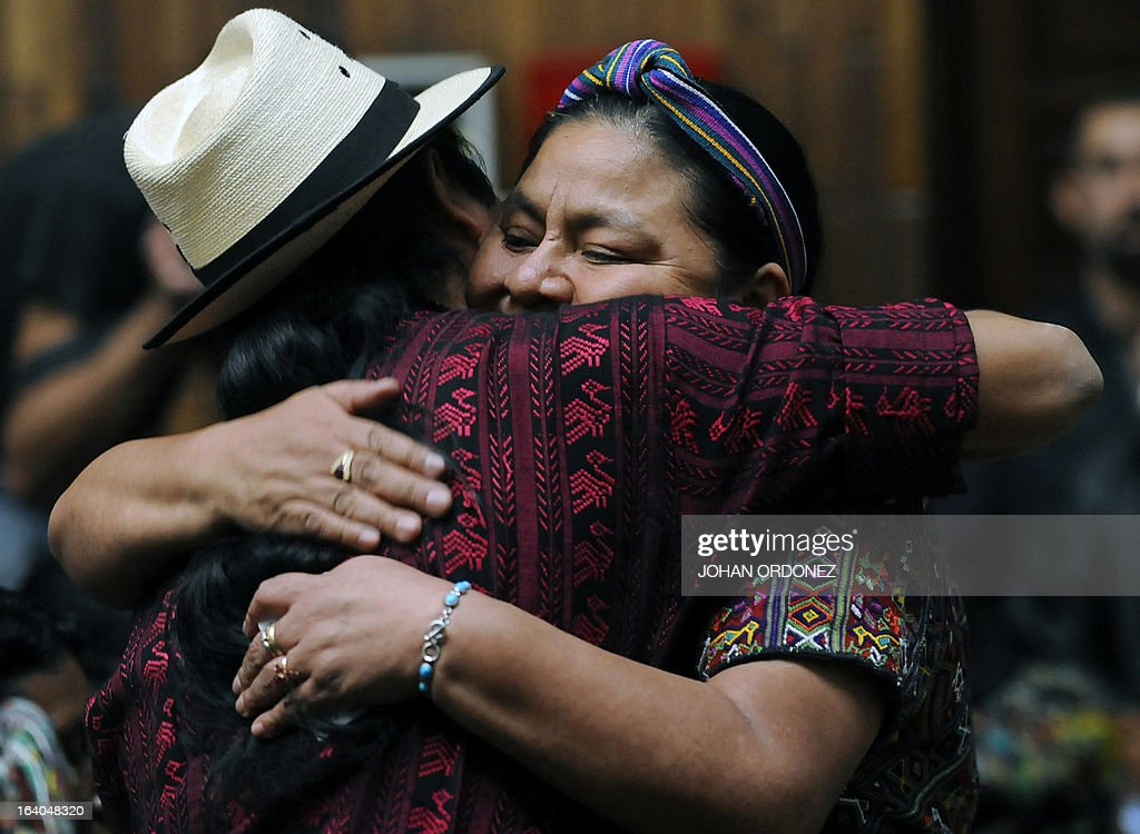 Guatemalan 1992 Nobel Peace Prize laureate Rigoberta Menchu hugs a relative of a victim of Guatemala's civil war during the trial against former Guatemalan de facto President (1982-1983), retired General Jose Efrain Rios Montt (not in frame) on charges of genocide, in Guatemala City on March 19, 2013. Rios Montt, who stands trial despite defense attempts to postpone the start of the historic proceedings, is accused of ordering the execution of 1,771 members of the indigenous Ixil Maya people in the Quiche region. The trial marks the first time genocide proceedings have been brought in relation to the 36-year civil war in Guatemala that ended in 1996, leaving an estimated 200,000 people dead, according to United Nations estimates. AFP PHOTO/Johan ORDONEZ