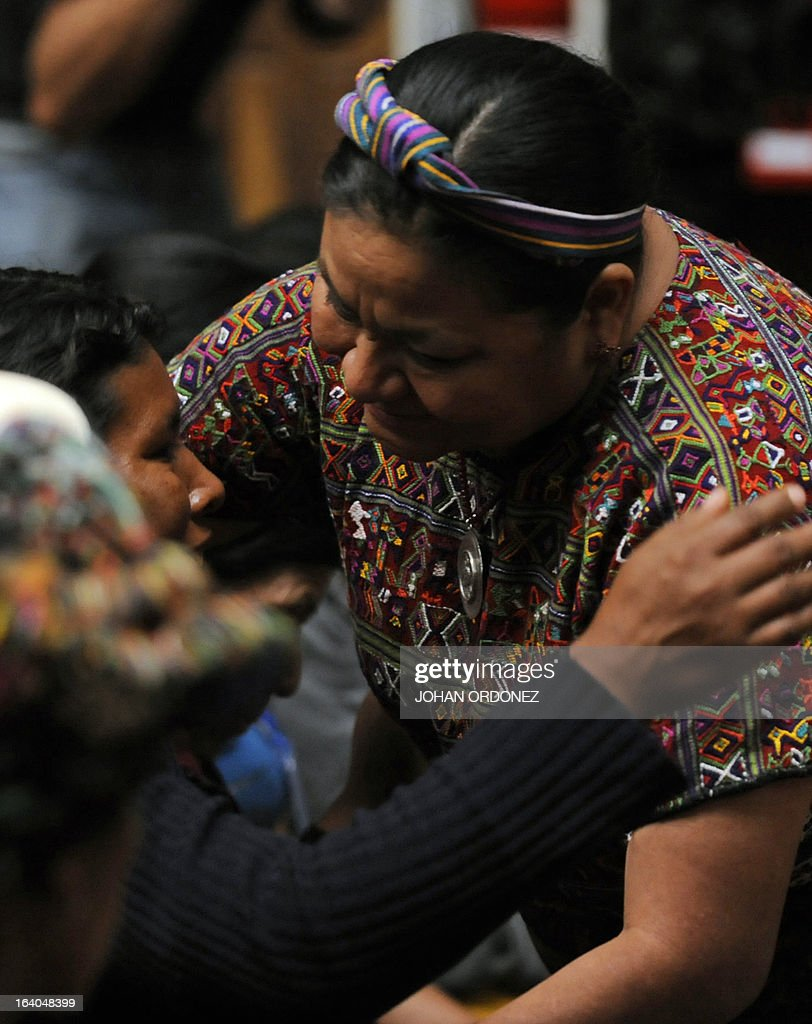 Guatemalan 1992 Nobel Peace Prize laureate Rigoberta Menchu (R) hugs a relative of a victim of Guatemala's civil war during the trial against former Guatemalan de facto President (1982-1983), retired General Jose Efrain Rios Montt (not in frame) on charges of genocide, in Guatemala City on March 19, 2013. Rios Montt, who stands trial despite defense attempts to postpone the start of the historic proceedings, is accused of ordering the execution of 1,771 members of the indigenous Ixil Maya people in the Quiche region. The trial marks the first time genocide proceedings have been brought in relation to the 36-year civil war in Guatemala that ended in 1996, leaving an estimated 200,000 people dead, according to United Nations estimates. AFP PHOTO/Johan ORDONEZ