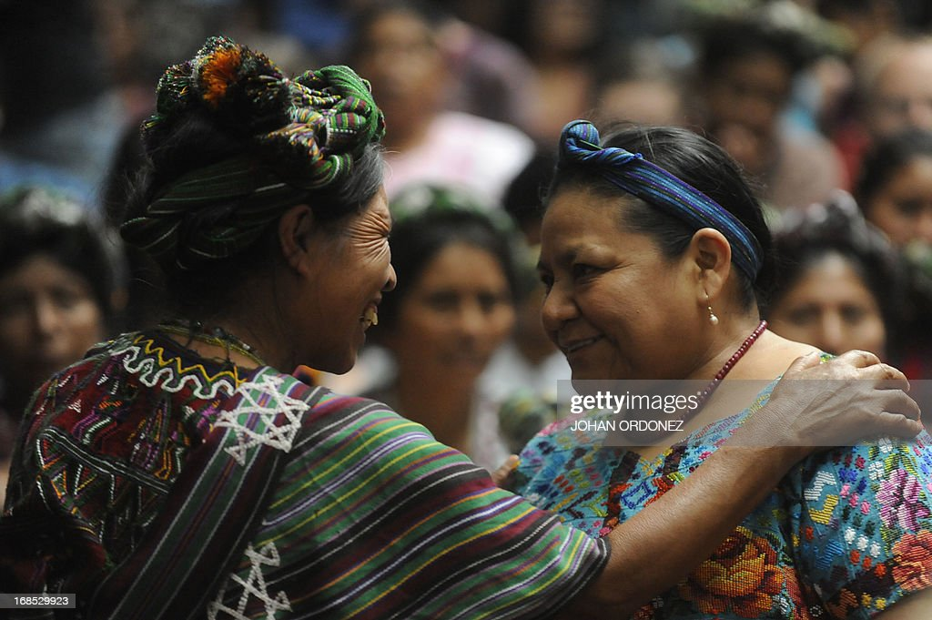 Guatemalan 1992 Nobel Peace Prize laureate Rigoberta Menchu (R) smiles with the relative of a victim of Guatemala's civil war during the trial against former Guatemalan de facto President (1982-1983), retired General Jose Efrain Rios Montt, on charges of genocide committed during his regime, in Guatemala City, on May 10, 2013. Rios Montt was found guilty of genocide and war crimes on Friday in a landmark ruling stemming from massacres of indigenous people in his country's long civil war. Rios Montt thus became the first Latin American convicted of trying to exterminate an entire group of people in a brief but particularly gruesome stretch of a war that started in 1960, lasted 36 years and left around 200,000 people dead or missing. AFP PHOTO / Johan ORDONEZ