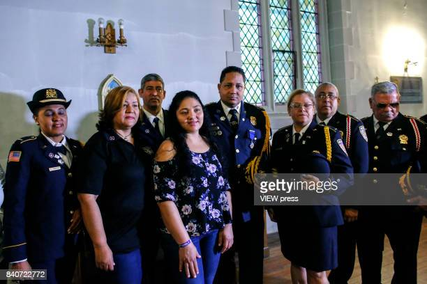 Guatemalan immigrant Amanda Morales poses with a group of firefighters at a vigil while she has taken refuge inside Holyrood Church in the Washington...