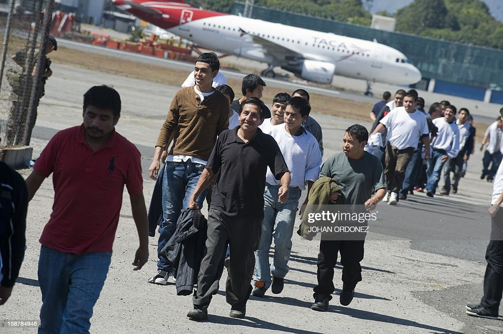 Guatemalan migrants deported from different parts of the US walk after disembarking from a plane in Guatemala City on December 28, 2012. Officials from the immigration department confirmed that in 2012 the number of Guatemalans deported from the United States was 40,635 compared to 30.855 in 2011. AFP PHOTO/Johan ORDONEZ