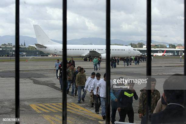 Guatemalan migrants deported from the US and northern Mexico walk from a plane to a processing center at an Air Force base in Guatemala City...