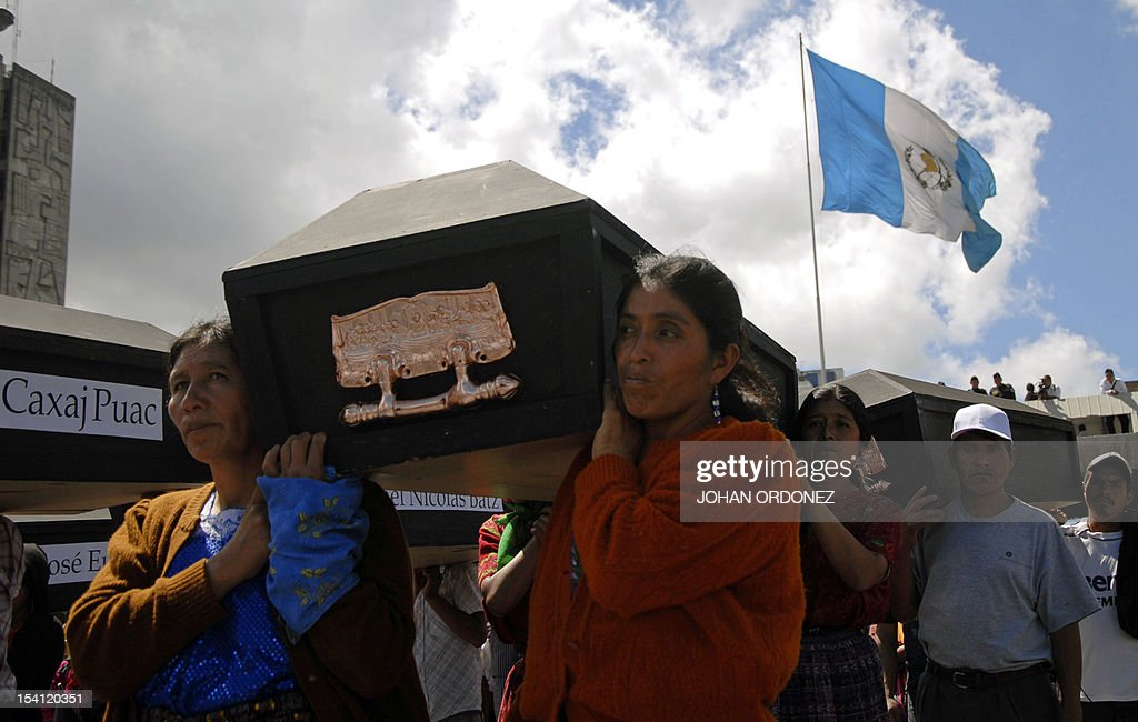 Guatemalan natives carry empty coffins during the 'Life and dignity' march in Guatemala City on October 14 following the killing last October 4 of...