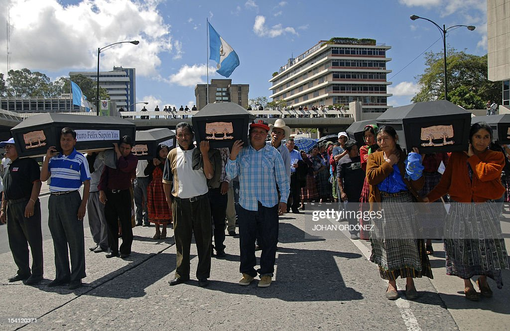 Guatemalan natives carry empty coffins while taking part in the 'Life and dignity' march in Guatemala City on October 14 to condemn the killing last...