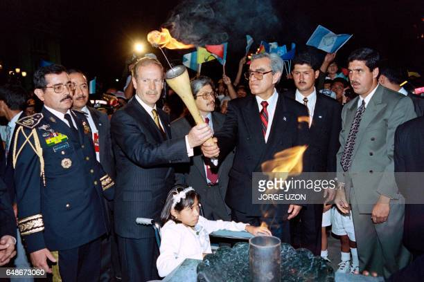 Guatemalan President Alvero Arzu lights a peace torch with Guatemalan National Revolutionary Unity commander Rolando Moran as a girl victim of the...