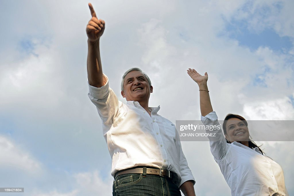 Guatemalan President Otto Perez Molina (L) and his Vice-President Raxana Baldetti wave during the commemoration of the first year of their administration on January 13, 2012 at La Alameda neighborhood in Guatemala City. AFP PHOTO Johan ORDONEZ