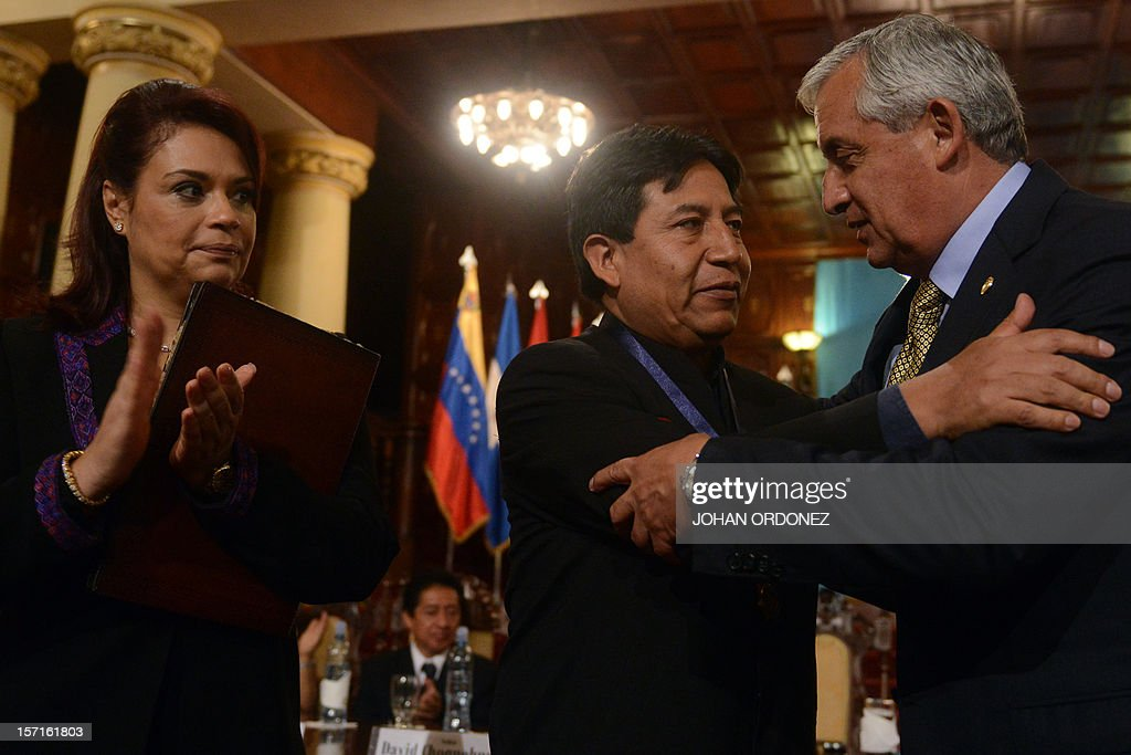 Guatemalan President Otto Perez Molina (R) greets Bolivia's Foreign Minister David Choquehuanca as Guatemala's Vice President Roxana Baldetti looks on during the opening ceremony of the X General Assembly of the Indigenous Fund at the Palace of Culture in Guatemala City on November 29, 2012. The Indigenous Fund, with head office in Bolivia, has worked for two decades and aims for agreements to define guidelines and strategies for the development of the indigenous people in Latin America. AFP PHOTO / Johan ORDONEZ