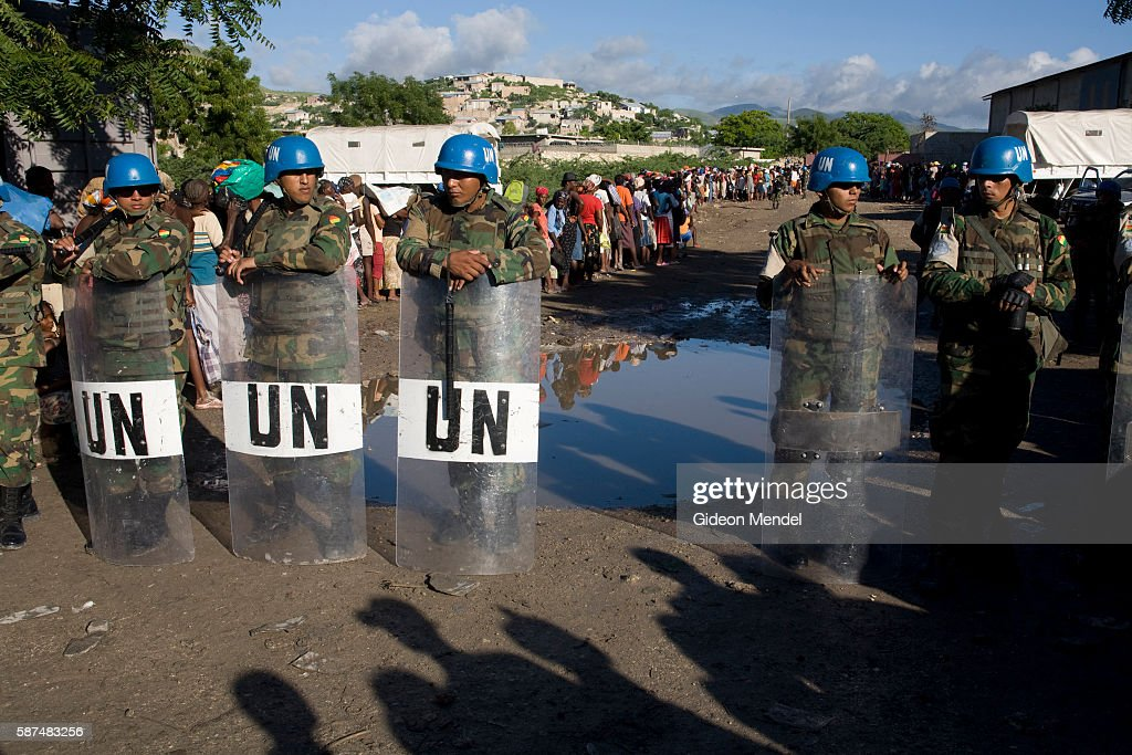 Guatemalan soldiers with riot gear who are part of MINUSTAH provide security as hundreds of hungry people queue for food relief in the flooded city...
