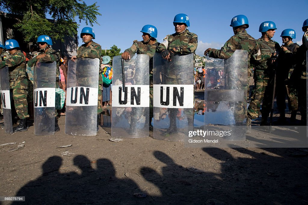 'Guatemalan soldiers with riot gear who are part of MINUSTAH provide security as hundreds of hungry people queue for food relief in the flooded city...