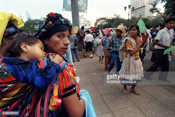 A Guatemalan woman watches a procession of Mayan communities in front of the National Palace in Guatemala City who came to watch the peacesigning...