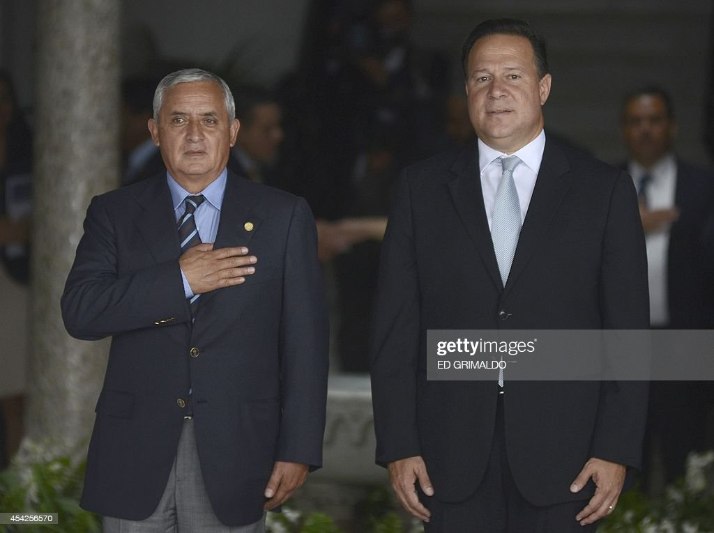 Guatemala's President Otto Perez Molina (L) and Panama's Juan Carlos Varela listen to their respective national anthems during the welcoming ceremony at the Palacio de las Garzas palace in Panama City, on August 27, 2014. Perez Molina is in Panama on oa ne-day official visit.