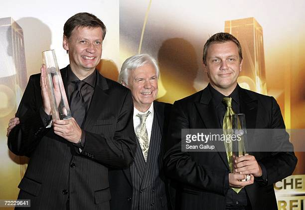 Guenther Jauch and Hape Kerkeling hold their awards for Best Entertainment Show as former sports presenter Dieter Kuerten looks on at the German...