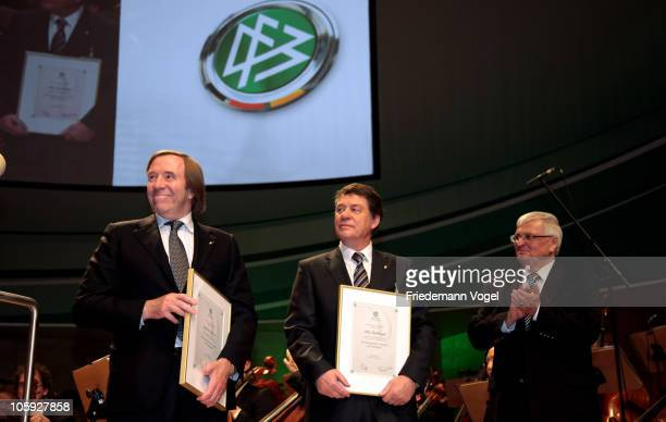 Guenther Netzer and Otto Rehhagel are honored by Theo Zwanziger president of the German Football Association during the DFB Bundestag at the...