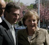 Guenther Oettinger Governor of the federal state of BadenWuerttemberg and German Chancellor Angela Merkel arrive for a trade conference at the...