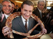 Guenther Oettinger state governor of BadenWuerttemberg and top candidate of the CDU wears a giant pretzel arround his neck in the parliament building...