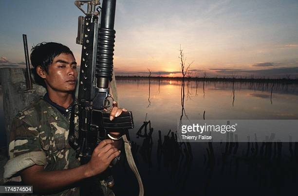 A guerilla soldier from the antiPhnom Penh Khmer Peoples National Liberation Front in front of a water reservoir in a socalled 'liberated area'
