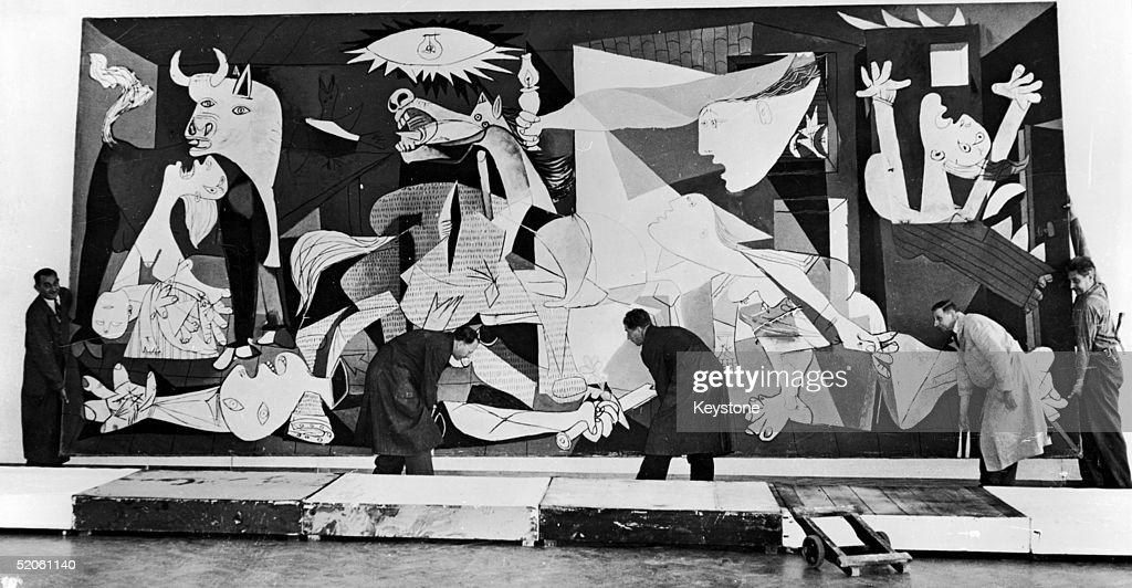 Guernica, perhaps the most famous painting by Pablo Picasso, being hung in the Municipal Museum in Amsterdam for an exhibition, 12th July 1956.