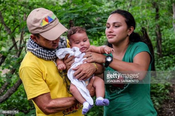 A FARC guerrilla couple takes care of a baby at their camp at the Transitional Standardization Zone in Pondores La Guajira department Colombia on...