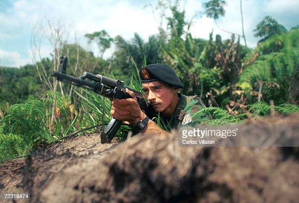 A guerrilla from the Revolutionary Armed Forces of Colombia guards a road March 7 2002 in the mountains near Bogota Sumapaz Colombia The group has...