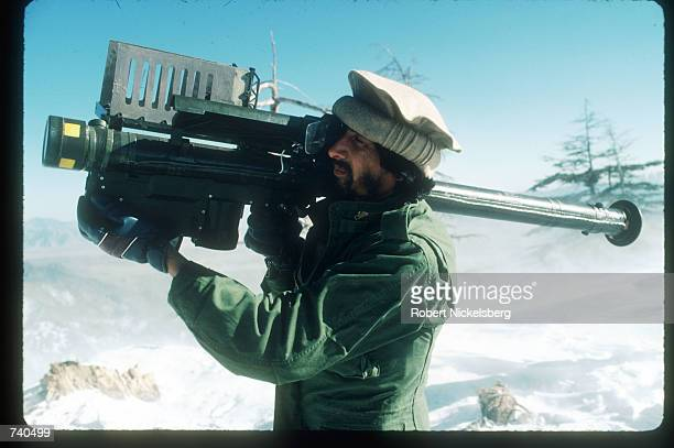 A guerrilla soldier aims a stinger missle at passing aircraft from a remote rebel base in the Safed Koh Mountains February 10 1988 in Afghanistan A...