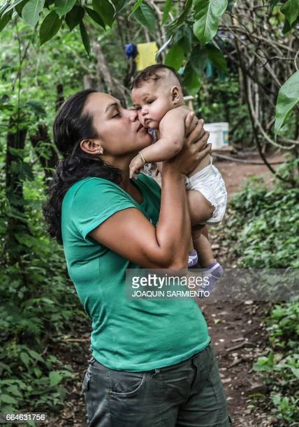 A FARC guerrilla takes care of a baby at their camp at the Transitional Standardization Zone in Pondores La Guajira department Colombia on April 3...