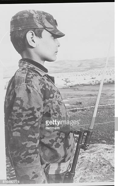 Two Views Amman Jordan This Arab youth seems to take his guerrilla training seriously as he stands at attention with rifle and bayonet in his...