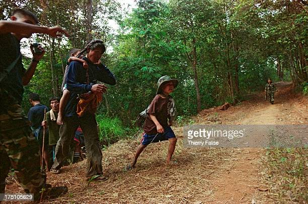 Guerrillas from the Karen National Union help fleeing villagers to cross a mined road used by the Burmese army The villagers were forced to abandon...