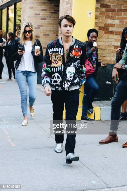 A guest attends New York Fashion Week wearing black printed bomber jacket on September 11 2017 in New York City
