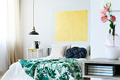 Guest bedroom with green tropical bedding and yellow artwork