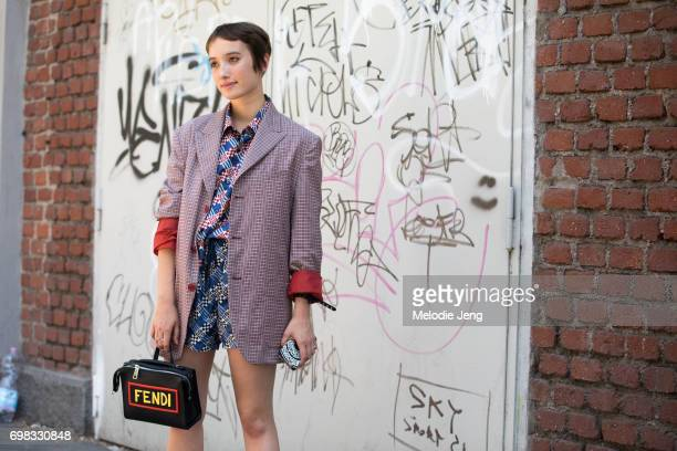 A guest carries a Fendi bag outside the Fendi show during Milan Men's Fashion Week Spring/Summer 2018 on June 19 2017 in Milan Italy