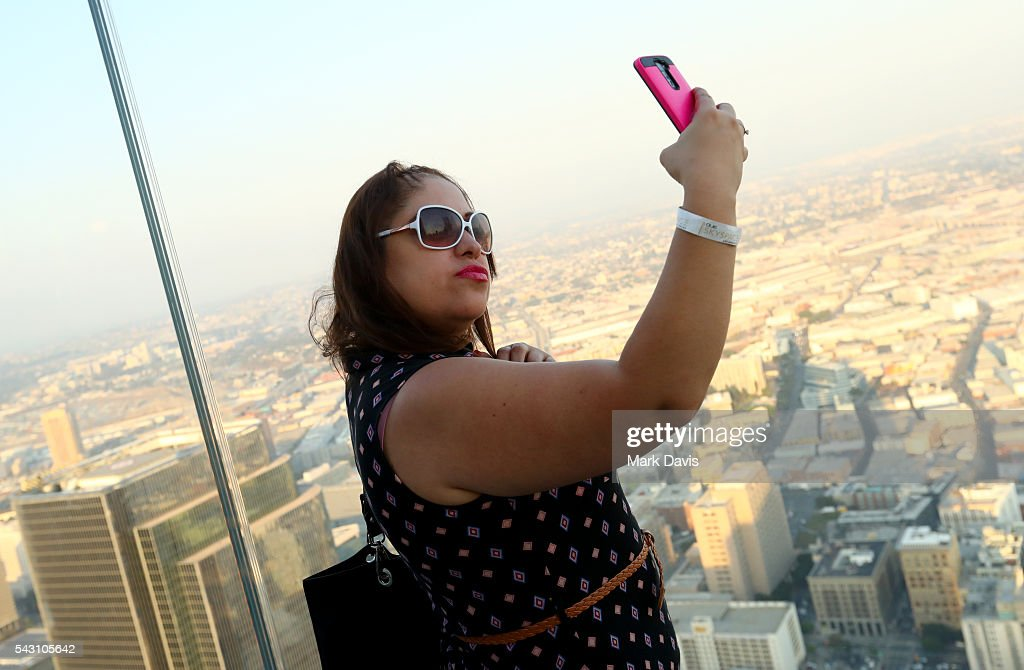 A guest enjoys the observation deck during the OUE Skyspace LA grand opening block party at OUE Skyspace LA on June 25, 2016 in Los Angeles, California.
