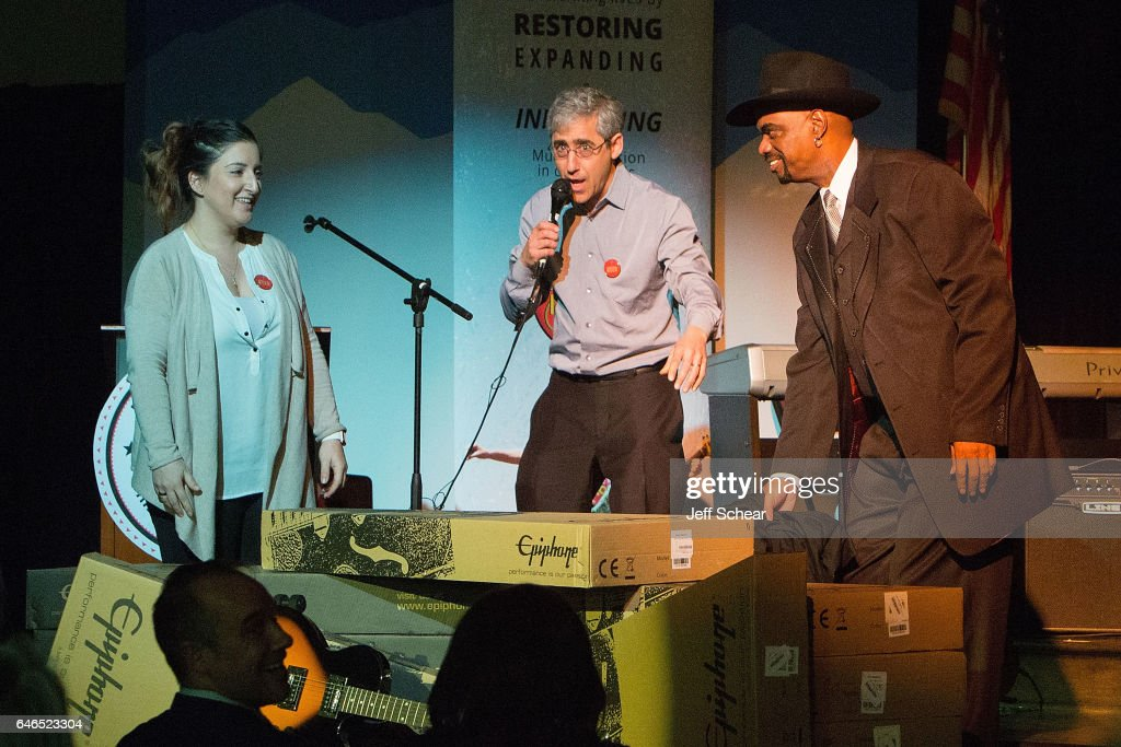 Guest, Founder of Kids Rock David Wish and (R) Nick Colionne unveil instruments at Chicago Public School Announces Music Program Expansion With Little Kids Rock at Franklin Fine Arts Center Auditorium on February 28, 2017 in Chicago, Illinois.