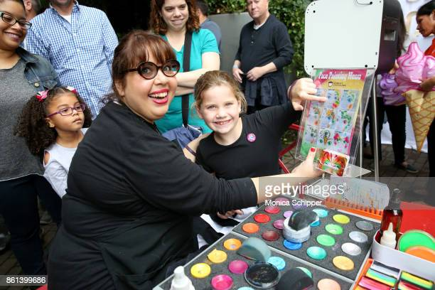 A guest gets an ice cream body paint during Family Ice Cream Fundae hosted by Mario Batali and Ayesha Curry at Private Park at Hudson on October 14...