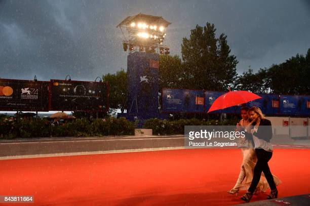 A guest gets escorted through the rain ahead of the 'Mektoub My Love Canto Uno' screening during the 74th Venice Film Festival at Sala Grande on...
