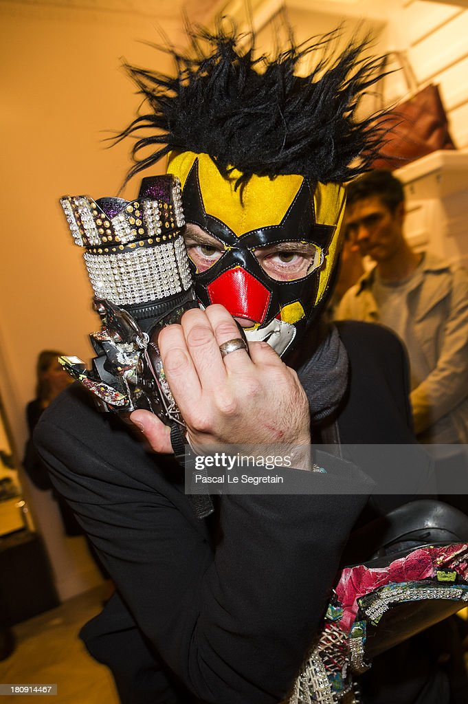 A guest holding a camera set with colors and novelty jewellery attends the Vogue Fashion Night Out event at boutique Roger Vivier on 29 Faubourg Saint-Honore, on September 17, 2013 in Paris, France.