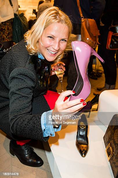 A guest holds a Roger Vivier shoe as she attends the Vogue Fashion Night Out event at boutique Roger Vivier on 29 Faubourg SaintHonore on September...