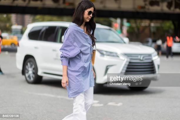A guest in front of a Lexus wearing a striped blue blouse seen in the streets of Manhattan outside Coach during New York Fashion Week on September 12...