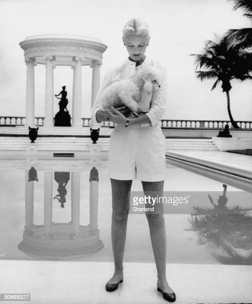 Guest in white shorts standing by her Palm Beach swimming pool with white poodle posing on black poolside sphinx