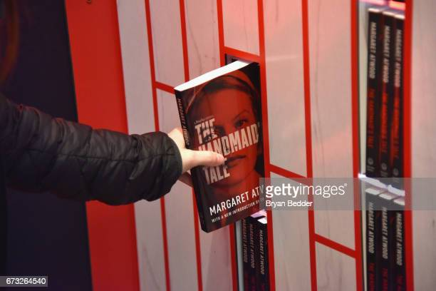 A guest interacts with an art installation designed by Paula Scher and Abbott Miller and book giveaway celebrating Hulu's 'The Handmaid's Tale' opens...