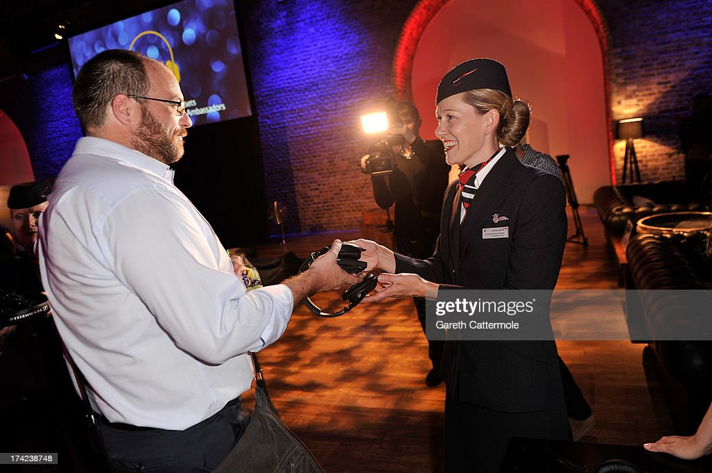 A guest is given headphones during the British Airways Silent Picturehouse launch at Vinopolis on July 22, 2013 in London, England.The pop-up film event shows movies that inspire travel.