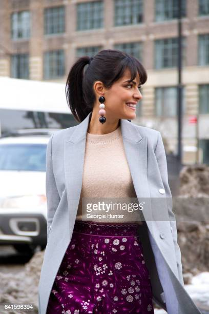 Guest is seen at Spring Studios outside the Lacoste show wearing high waisted purple floral three quarter length skirt pastel blue coat peach sweater...