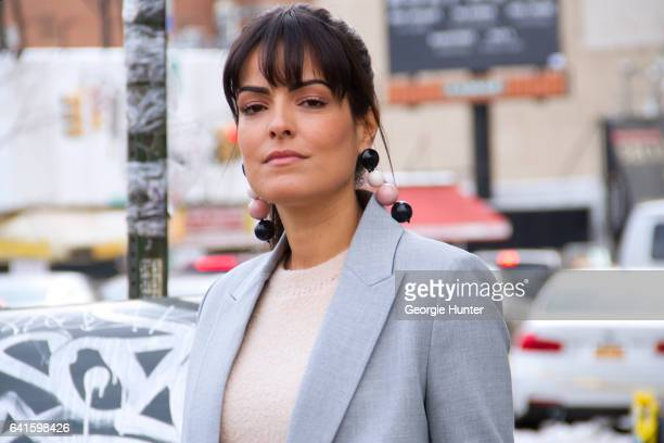 Guest is seen at Spring Studios outside the Lacoste show wearing pastel blue coat peach sweater and black pink and white circular ball drop earrings...